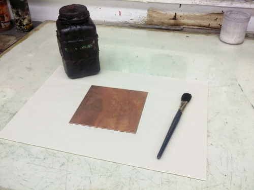 Copper placed on newsprint, with brush and a bottle of liquid ground.